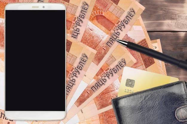 Купюры 5 белорусских рублей и смартфон с кошельком и кредитной картой