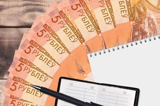 5ベラルーシルーブル紙幣ファンとメモ帳と連絡帳と黒ペン。財務計画と事業戦略の概念