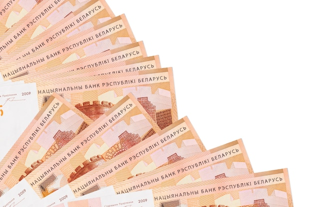 Купюры 5 белорусских рублей лежат изолированно на белой стене с копией пространства, сложенными в веер крупным планом. понятие времени выплаты жалованья или финансовые операции