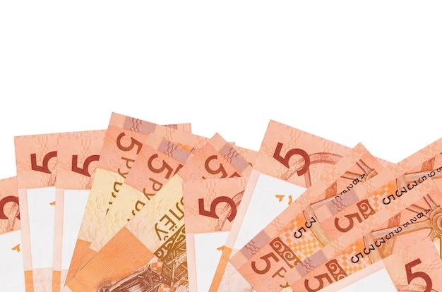 Купюры 5 белорусских рублей лежат в нижней части экрана на белом фоне с копией пространства