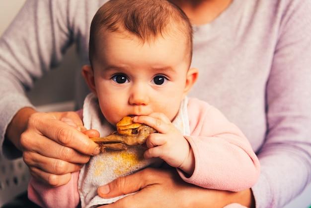 5-месячный ребенок ест куриную ножку, используя метод blw на отлучении от ребенка.