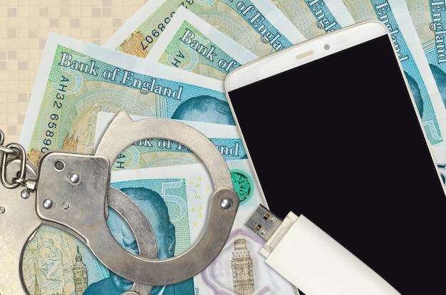 5英国ポンド紙幣と警察の手錠付きスマートフォン