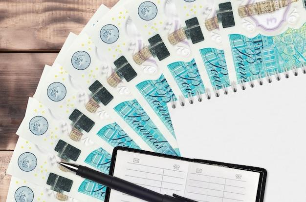 Вентилятор банкнот 5 британских фунтов и блокнот с записной книжкой и черной ручкой