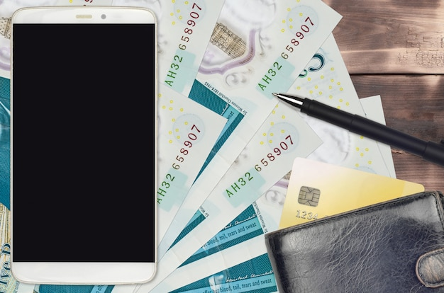 5 british pounds bills and smartphone with purse and credit card. e-payments or e-commerce concept. online shopping and business with portable devices