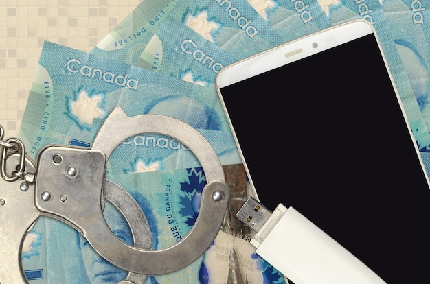5カナダドル札と警察の手錠付きスマートフォン。ハッカーのフィッシング攻撃、違法な詐欺、またはオンラインスパイウェアのソフト配布の概念