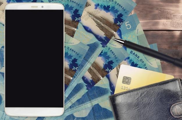 Купюры 5 канадских долларов и смартфон с кошельком и кредитной картой
