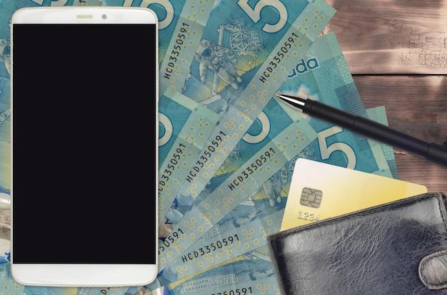 Купюры 5 канадских долларов и смартфон с кошельком и кредитом