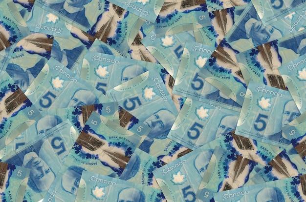 5 canadian dollars bills lies in big pile. rich life conceptual wall. big amount of money