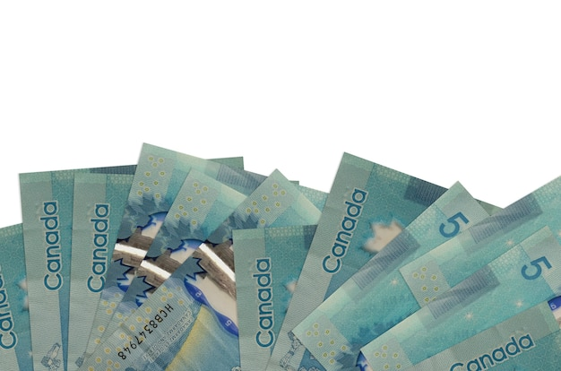 5 canadian dollars bills lies on bottom side of screen isolated on white wall with copy space.