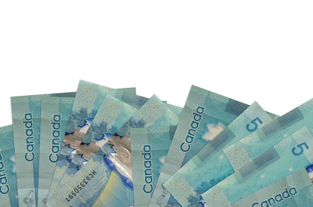 Купюры 5 канадских долларов лежат на нижней стороне изолированного экрана. фон баннера шаблон для бизнес-концепций с деньгами