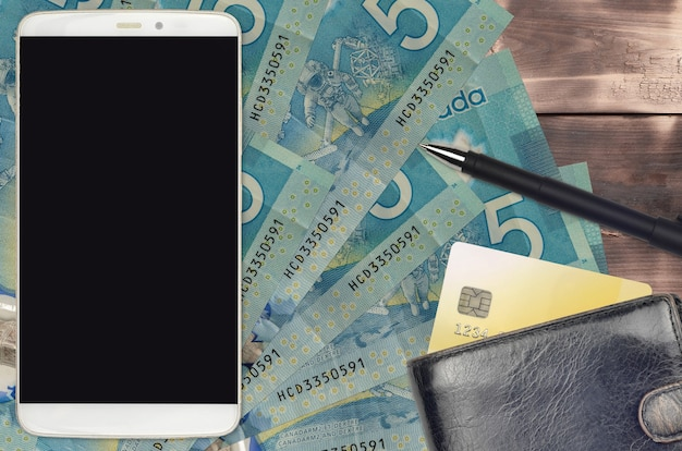 5 canadian dollars bills and smartphone with purse and credit