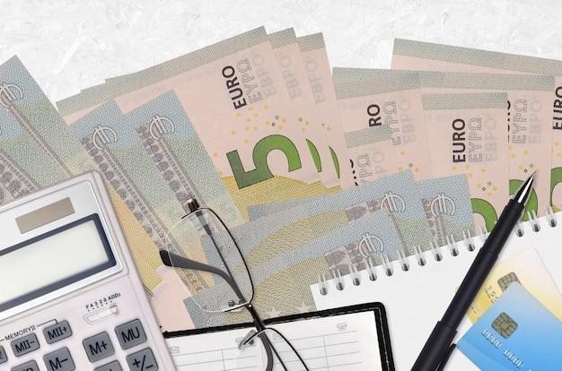 Купюры 5 евро и калькулятор с очками и ручкой. концепция сезона уплаты налогов или инвестиционные решения. финансовое планирование или бухгалтерские документы