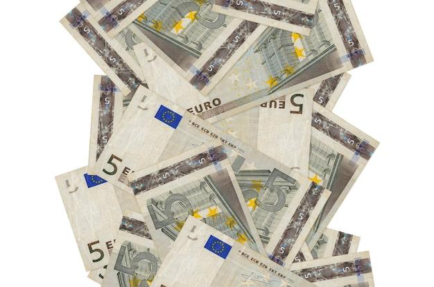 白で隔離されて飛んでいる5ユーロ紙幣。多くの紙幣が左右に白いコピースペースで落ちています