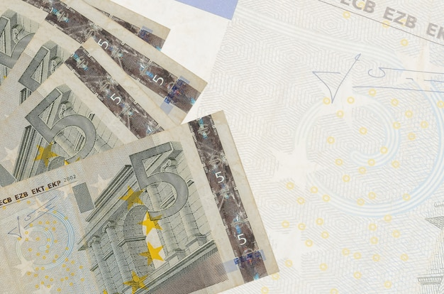 5 euro bills lies in stack on wall of big semi-transparent banknote. abstract business wall with copy space