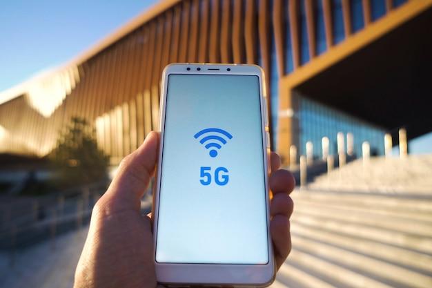 ブロードキャストアンテナと画面上のスマートフォンと5 g信号シンボルを持っている男の手。高速モバイルweb接続技術コンセプト