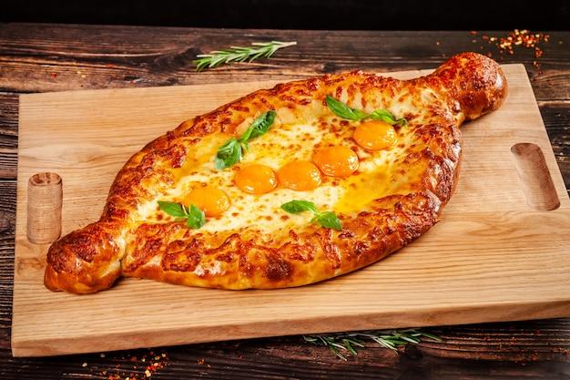 グルジア料理。木の板に、卵黄5個の大きなkhachapuri。大企業向けのレストランでの料理。背景画像のコピースペース