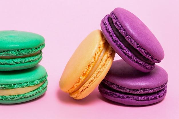5 покрашенных macaroons на розовой предпосылке.
