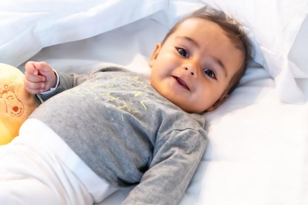 5-месячный кавказский ребенок, улыбающийся в белой постели, только что проснулся, серая футболка и мяч для игры