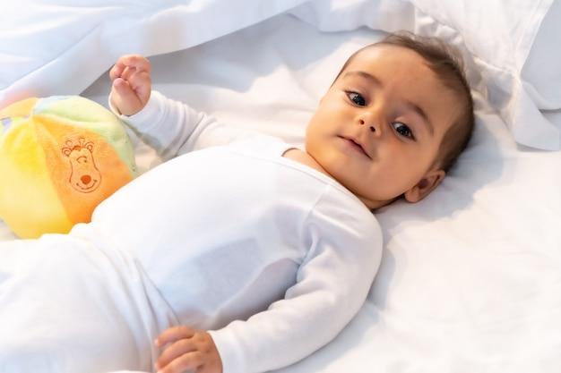 5-месячный кавказский ребенок, улыбающийся в белой постели, только что проснулся, белое боди и мяч для игры