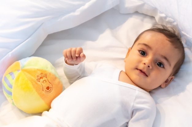 5 month old caucasian baby smiling in white bed just woken up, white bodysuit and a ball to play