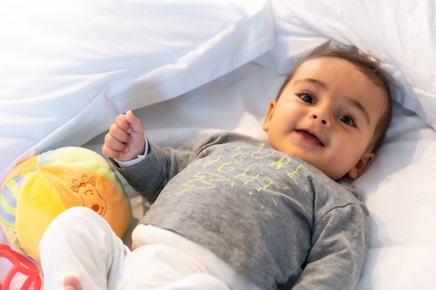 5 month old caucasian baby smiling in white bed just woken up
