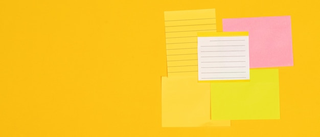 5 sheets of note paper laid on a yellow background