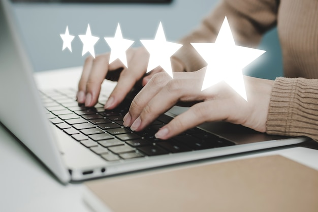 5 star rating. business woman hand working on laptop with five star button on visual screen to review good rating, digital marketing, good experience, positive thinking and customer feedback concept