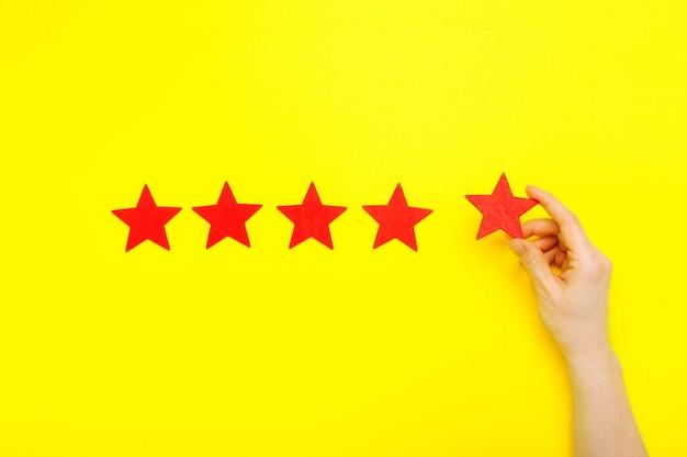 Повышение рейтинга на 5 звезд, концепция обслуживания клиентов. рука клиента показывает 5-звездочный символ для повышения рейтинга сервиса. пять красных звезд отличный рейтинг на желтом фоне. концепция удовлетворенности