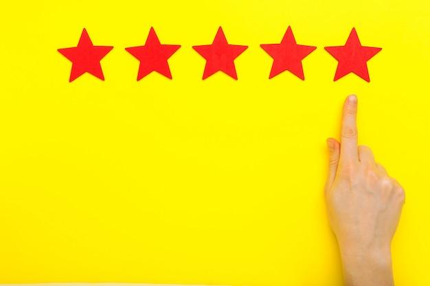 5つ星の評価、顧客体験のコンセプトを増やします。クライアントの手は、サービスの評価を上げるために5つ星のシンボルを表示しています。