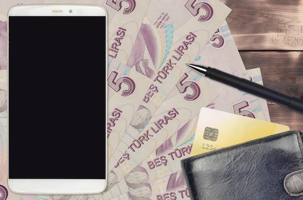 5トルコリラ紙幣と財布とクレジットカード付きのスマートフォン