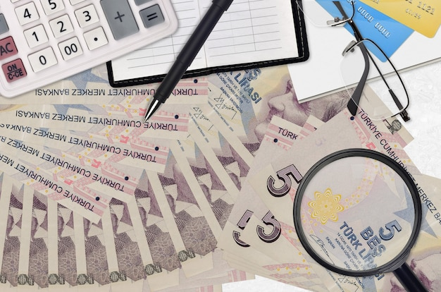 5 turkish lira bills and calculator with glasses and pen. tax payment season concept or investment solutions.