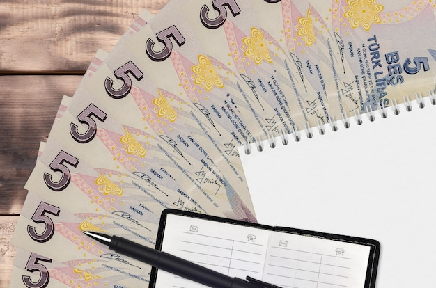 Вентилятор банкнот 5 турецких лир и блокнот с контактной книгой и черной ручкой