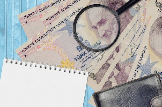 5 turkish lira bills and magnifying glass with black purse and notepad. concept of counterfeit money. search for differences in details on money bills to detect fake money