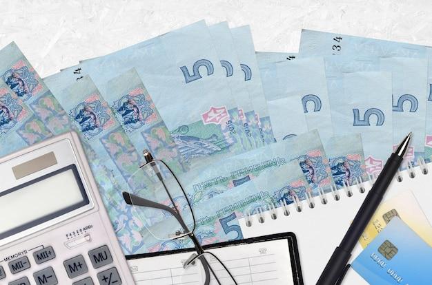 Купюры 5 украинских гривен и калькулятор с очками и ручкой. концепция уплаты налогов или инвестиционные решения. финансовое планирование или бухгалтерские документы