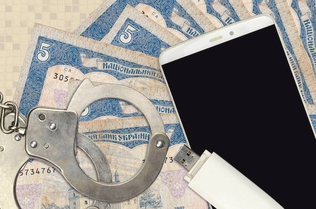 5ウクライナグリブナ紙幣と警察の手錠付きスマートフォン