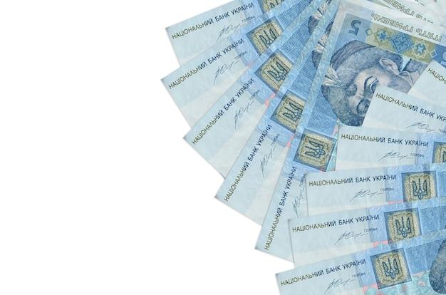 5ウクライナグリブナの請求書はコピースペースのある白い壁に隔離されています。 。大量の自国通貨資産