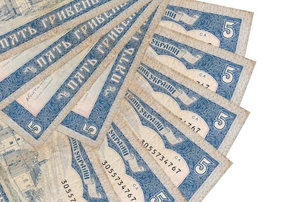 Банкноты 5 украинских гривен лежат изолированно на белой стене с копией пространства, сложенными в форме вентилятора крупным планом. концепция финансовых операций