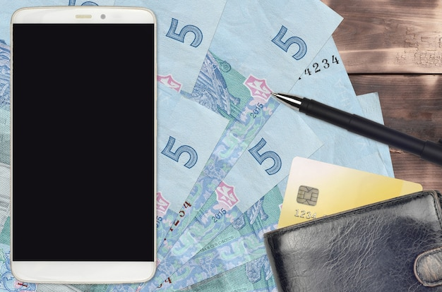 5 ukrainian hryvnias bills and smartphone with purse and credit card. e-payments or e-commerce concept. online shopping and business with portable devices usage