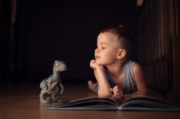 A 5 year old boy plays with a dinosaur