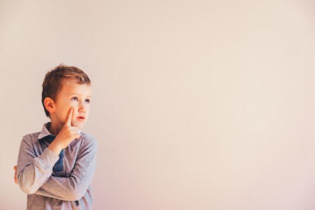 コピースペース領域の白い壁に、非常に表現力豊かな思慮深いジェスチャーを持つ5歳の少年。