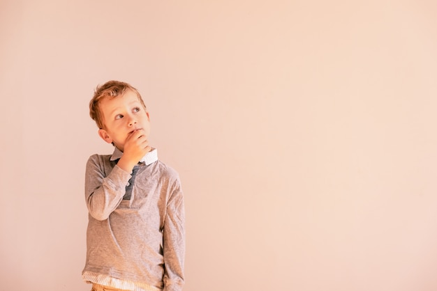 5 year old boy with very expressive thoughtful gesture, on white background with copy space area.