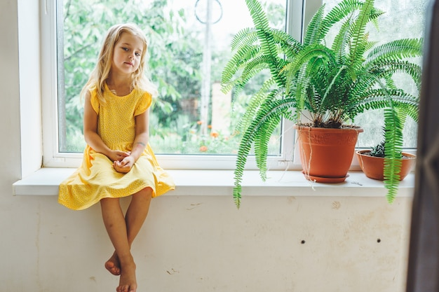 5 years old blonde girl sit on the windowsill with sad face. quarantine, lockdown. stay at home.