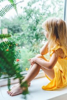 5살짜리 금발 소녀가 습하고 추운 비오는 날 창밖을 바라보고 있습니다.
