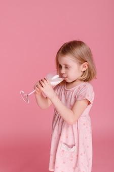 5 세 소녀는 분홍색 표면에 유리에서 우유를 마신다