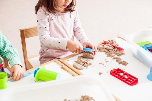 5歳の女の子が幼稚園でキネティックサンドで遊ぶ