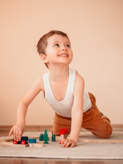 5 years old little boy playing with wooden train on floor and looking up.