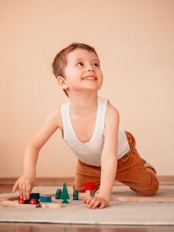 床に木製の電車で遊んで見上げる5歳の男の子。