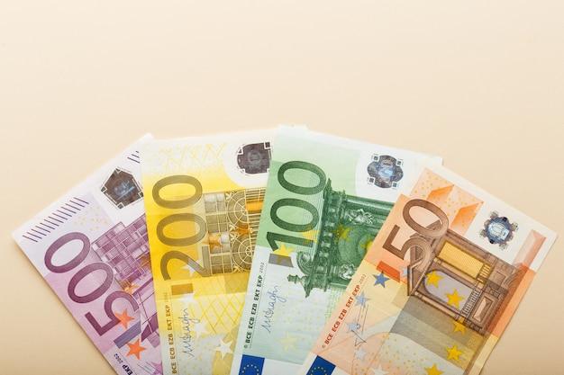 Банкноты 50, 100, 200, 500 евро на бежевом фоне вид сверху с копией пространства. деньги, бизнес, финансы, сбережения, банковское дело. обменные курсы.
