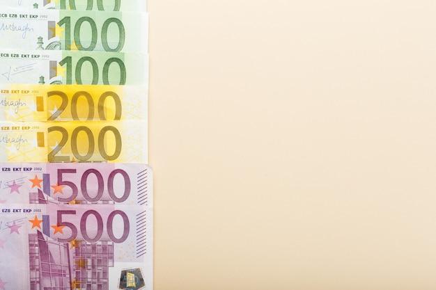 복사 공간 베이지 색 배경 상위 뷰에 50, 100, 200, 500 유로 지폐. 돈, 비즈니스, 금융, 저축, 금융 개념. 환율.