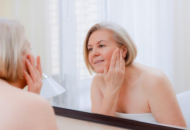 50〜60年後の浴室のスキンケアの後自宅で彼女の顔のミラーに手で肖像画かなり年配の女性